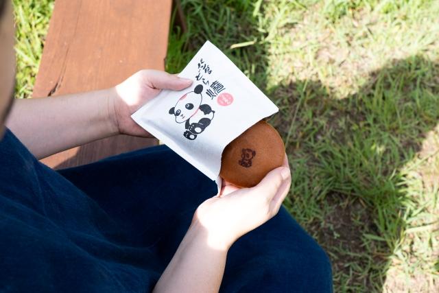 パンダのどら焼きを持った男性の写真